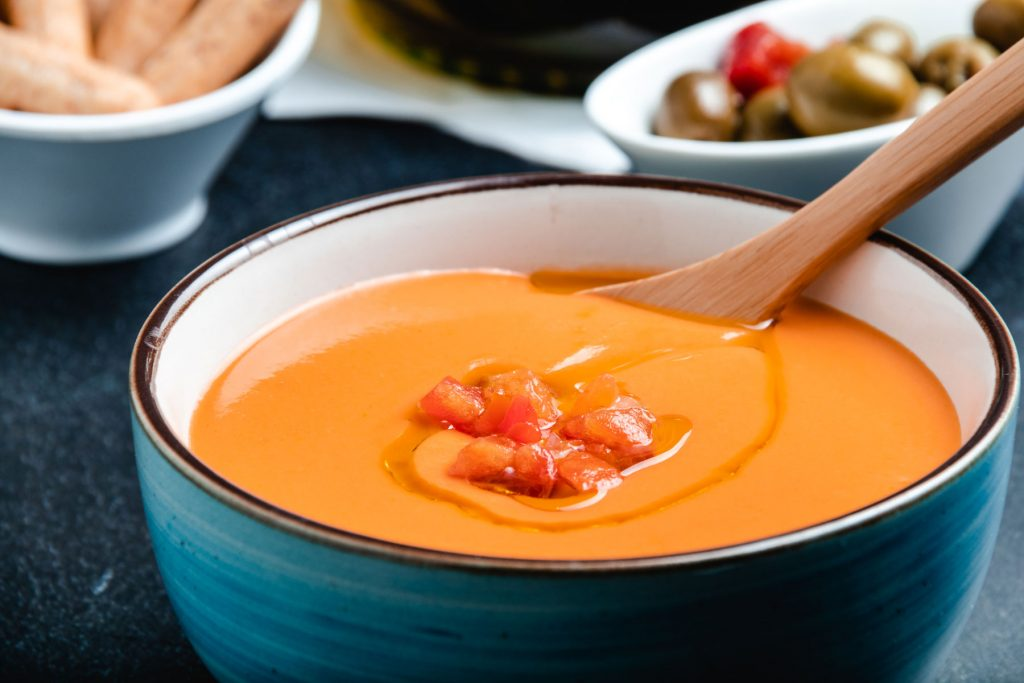 salmorejo in a bowl and a wooden spoon in it